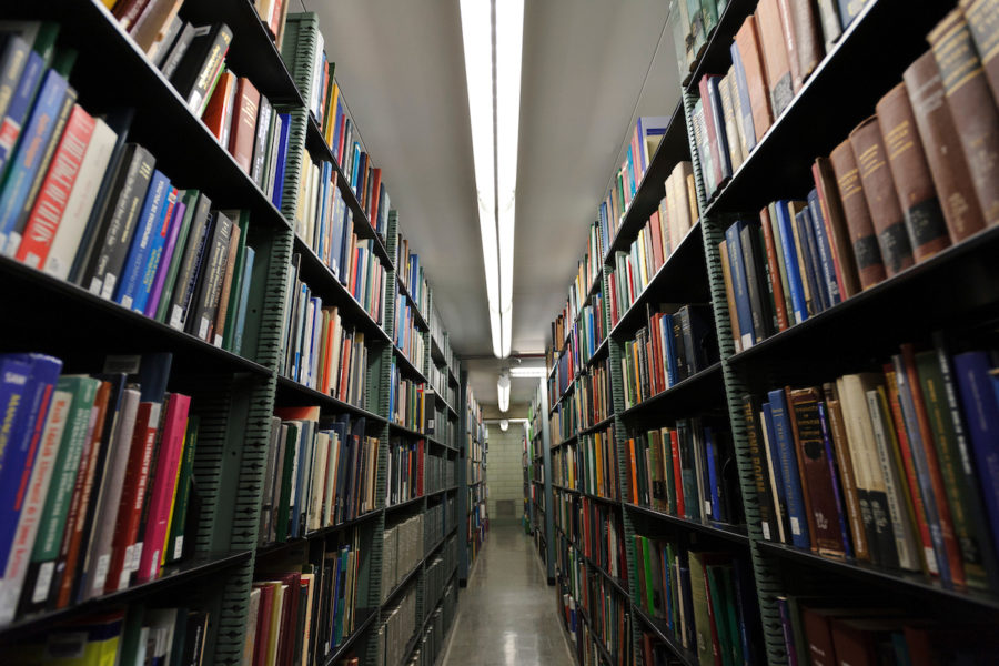 Overhead lighting shines down upon rows of books shelved in one of the many maze-like stacks in Memorial Library at the University of Wisconsin-Madison